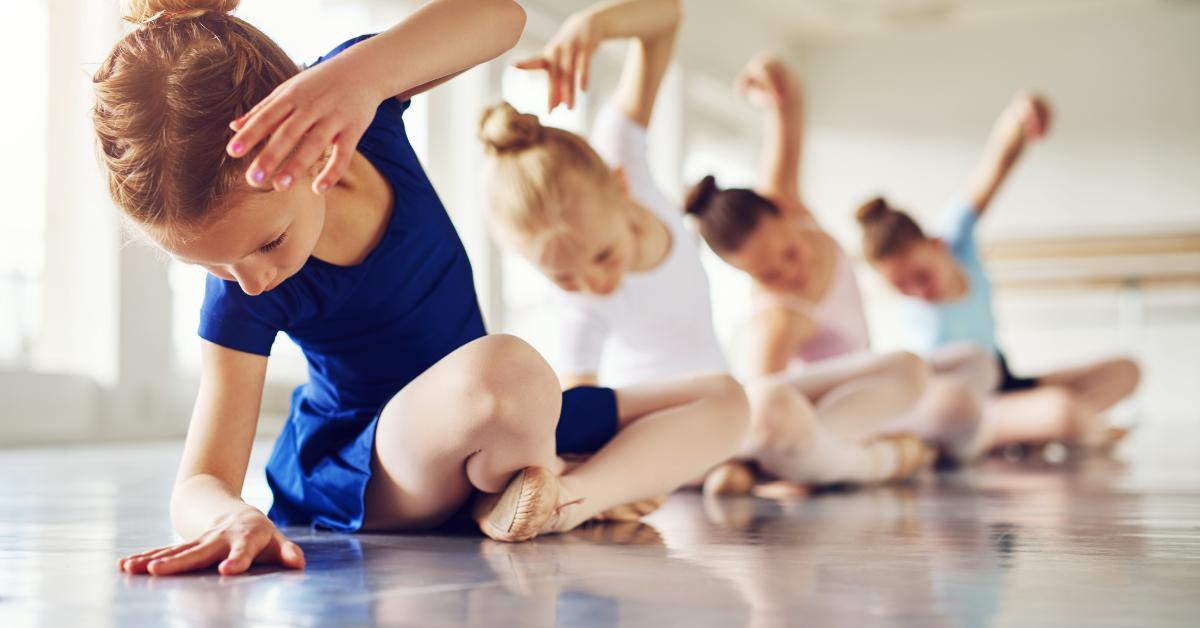 Child ballerinas sat down stretching